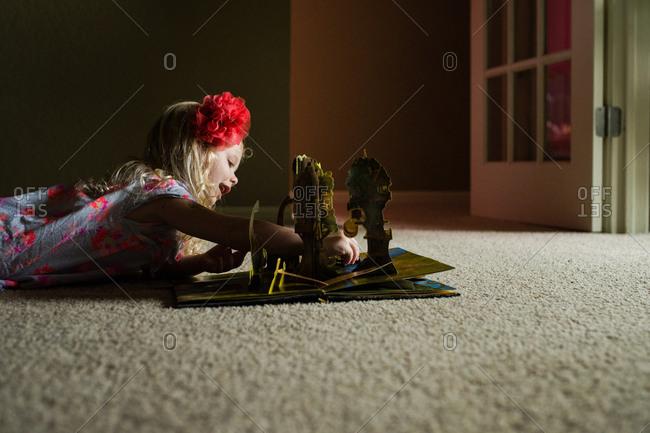 Girl on floor reading pop up book