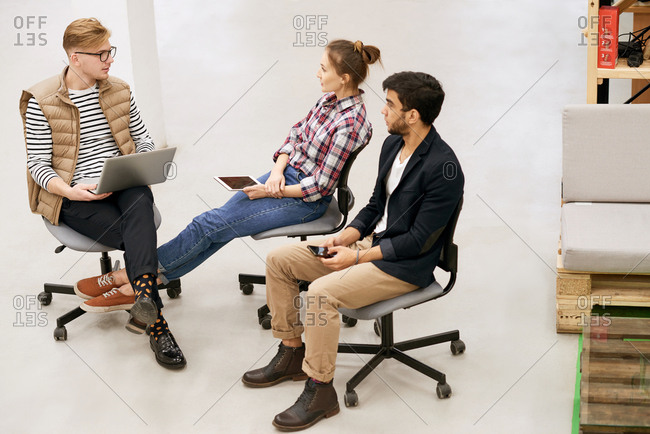 Group of young creative workers having informal meeting in office