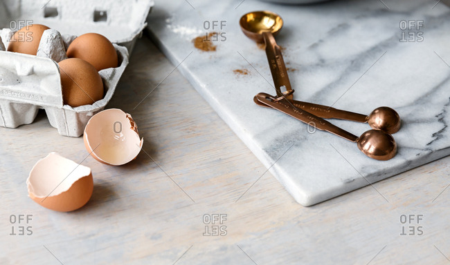 Cracked egg shell with measuring spoons side angle