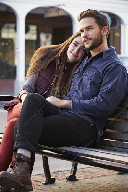 A young man and a young woman hugging, sitting on a bench in an urban environment