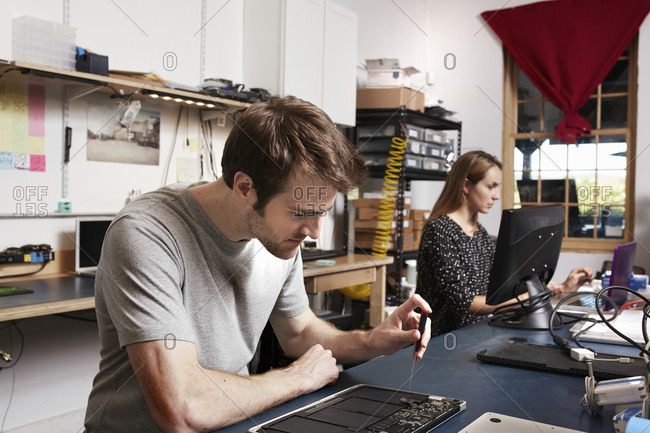 A young man and woman working at a bench in a technology lab