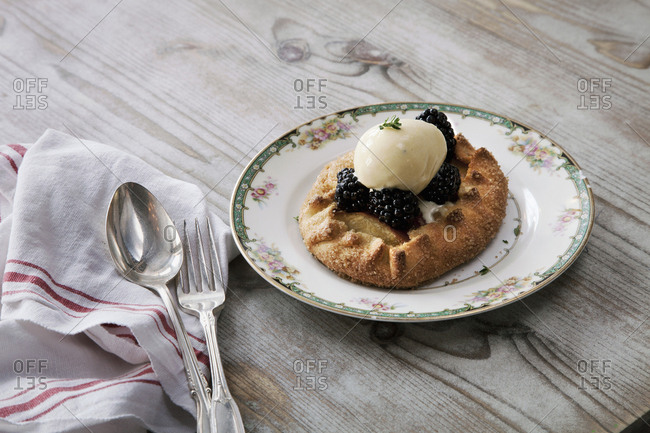 A pastry desert with fruit and ice cream on a china plate on a tabletop