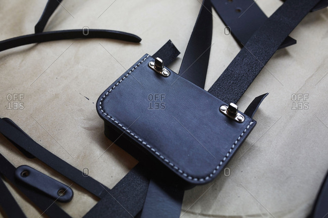 A handmade blue leather bag, strap, component part parts, scissors and hand tools