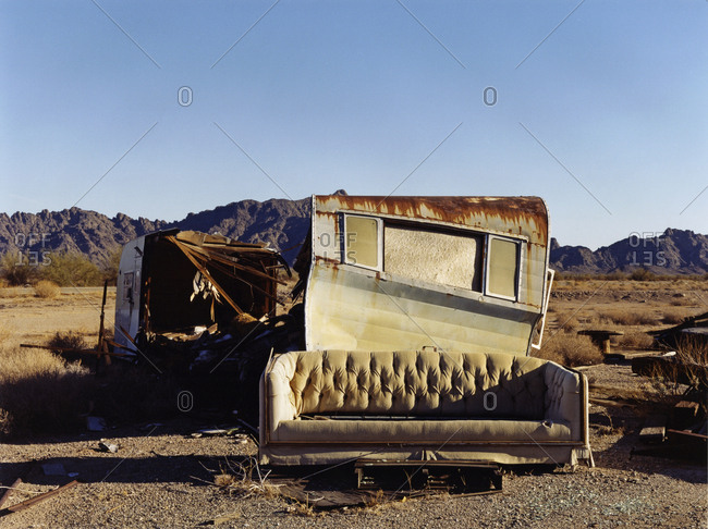 A ruined caravan, with rusting roof, a shelter, and a sofa