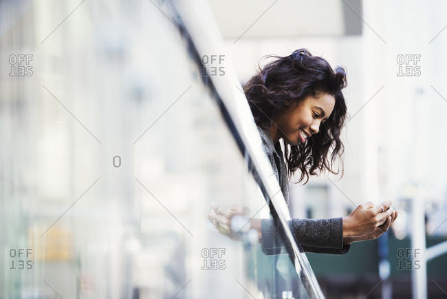 A young man leaning over a balcony rail looking at a cellphone and smiling