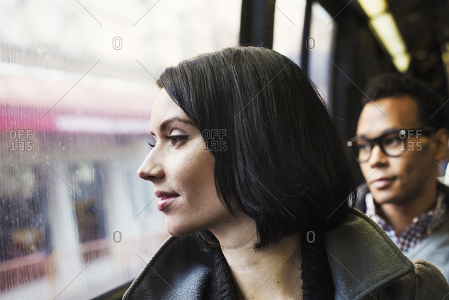 A woman sitting on public transport looking out of the window, with a young man in the background