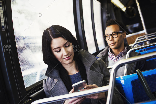 A young woman and a young man sitting on public transport, one looking at a cellphone and one looking away