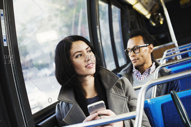 A young man and a young woman sitting on public transport holding their cellphones and looking around
