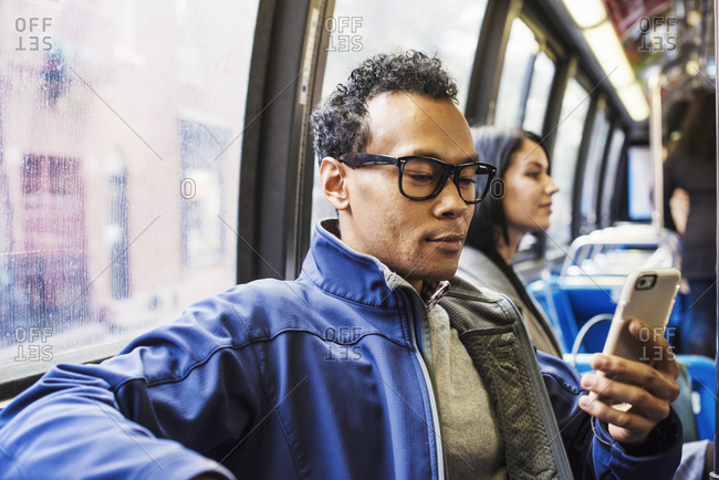 A young man and a young woman sitting on public transport looking at their cellphones