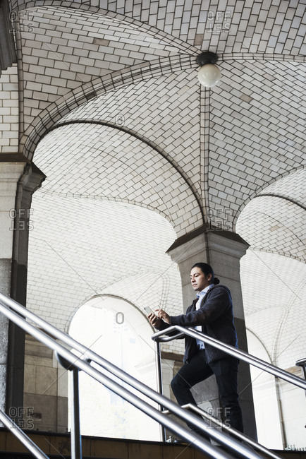 A young man standing on a stair under an archway, looking at his mobile phone