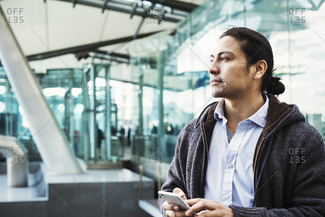 A young man holding his mobile phone, standing on a busy walkway