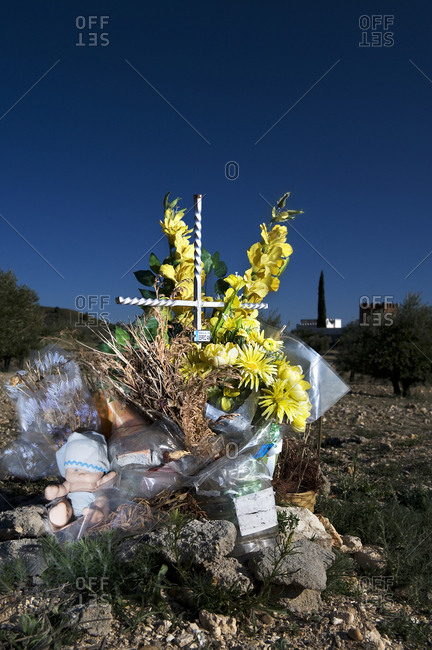 Latin cross surrounded with flowers and items to remember those who die on the road, Spain
