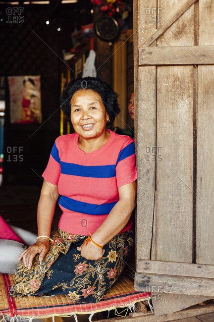 Tha Kaek, Laos - November 26, 2010: Typical lao middle aged woman smiling to the camera at the entrance of her house in Tha Kaek, Laos