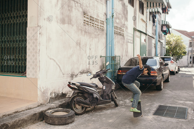 Asia - February 5, 2017: A girl practicing her kick flip in an alleyway