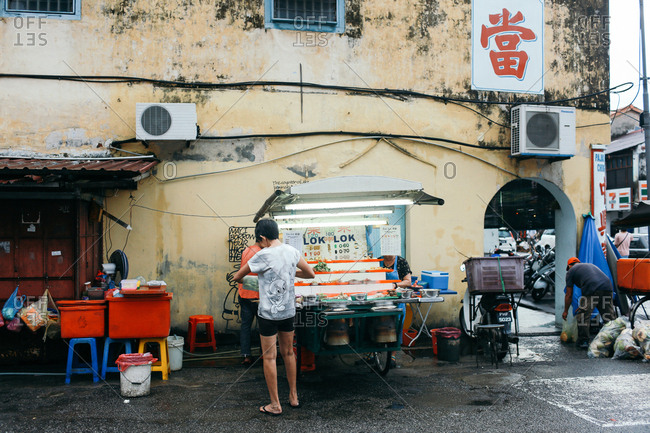 Penang, Malaysia - December 22, 2016: Street vendors opening their stands after the rain stopped