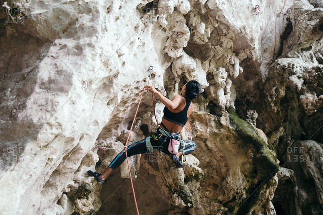 Thailand - January 14, 2017: A climber looks to clip her next draw