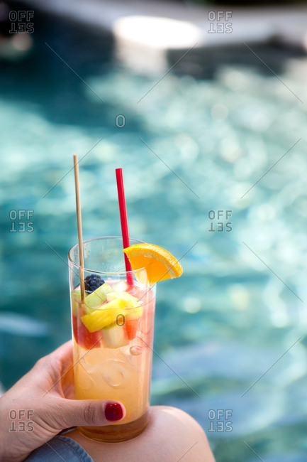 Woman holding cocktail with pool in background