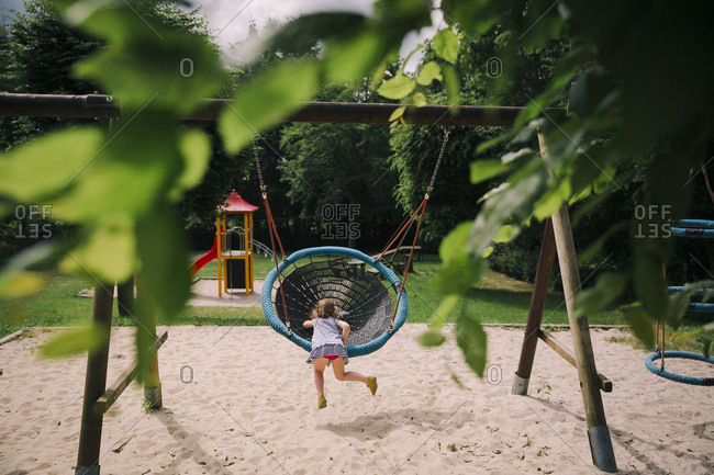 Girl swinging in rural playground