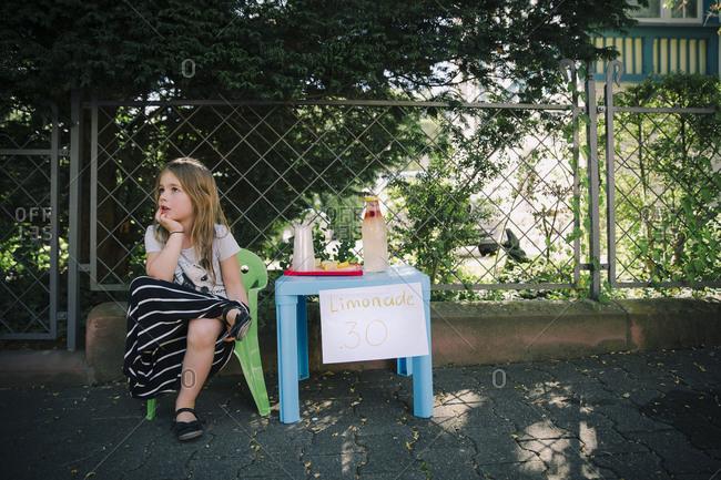 Girl waiting at her lemonade stand