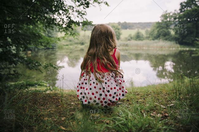 Girl by a pond in rural setting