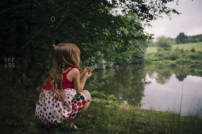 Girl kneeling by pond in rural setting