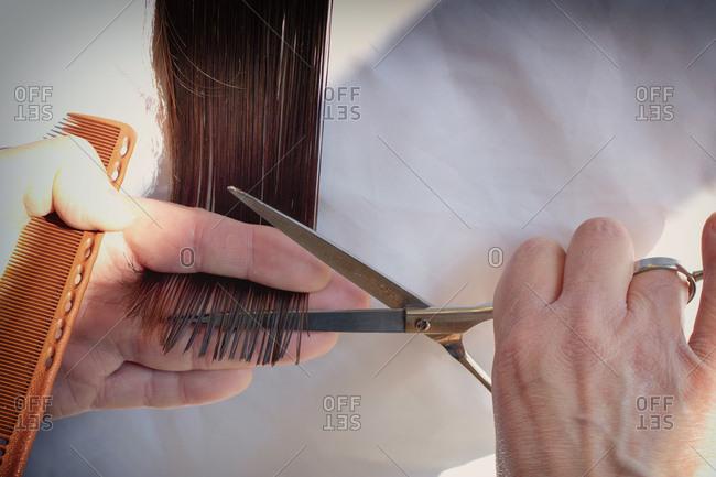 Hairdresser cutting woman's hair scissors stylist