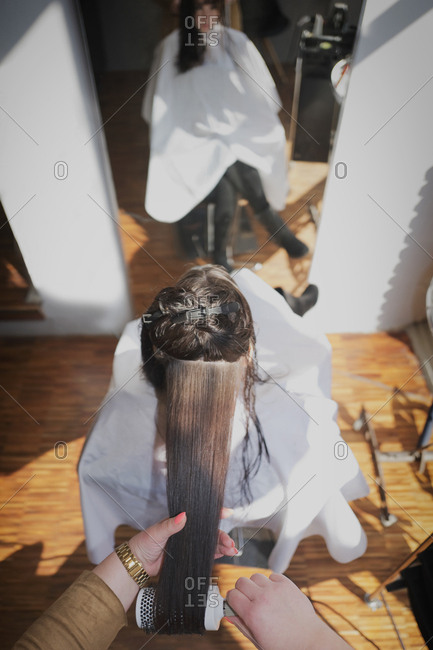Hairdresser woman combing long hair brushing salon