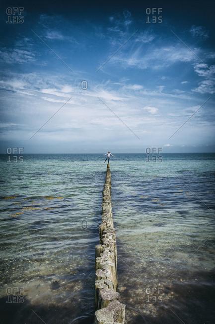 Girl standing on wooden piling piles sea ocean