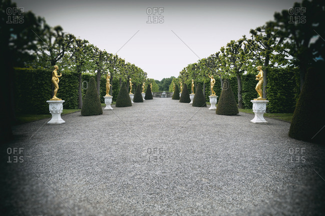 Hanover, Germany - May 18, 2016: Palace gardens golden sculpture statues hedgerow