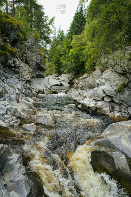 River rocks fast flowing forest highlands Scotland
