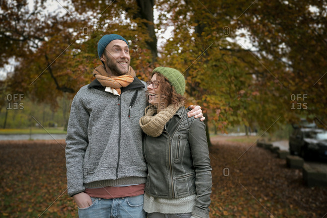 Young heterosexual couple autumn laughing 20s tree