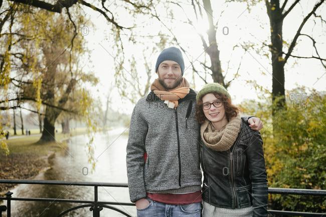 Heterosexual couple bridge hugging smiling 30s 20s