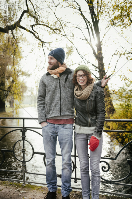Heterosexual couple autumn river bridge laughing