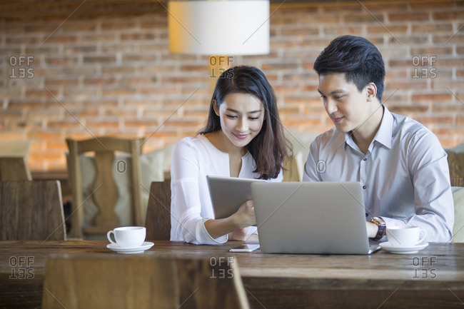 Young man and woman using digital tablet and laptop in cafe