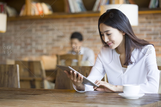 Young woman using digital tablet in cafe
