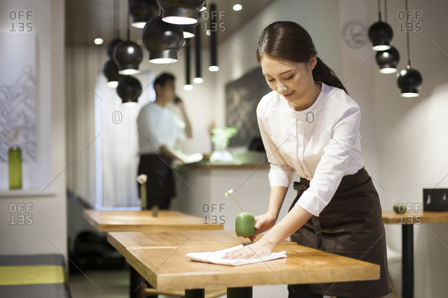 Young waitress wiping table