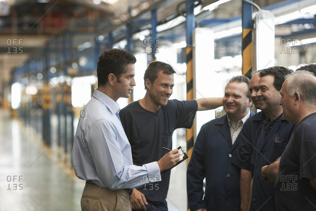 Man Talking to Workers in Automotive Plant