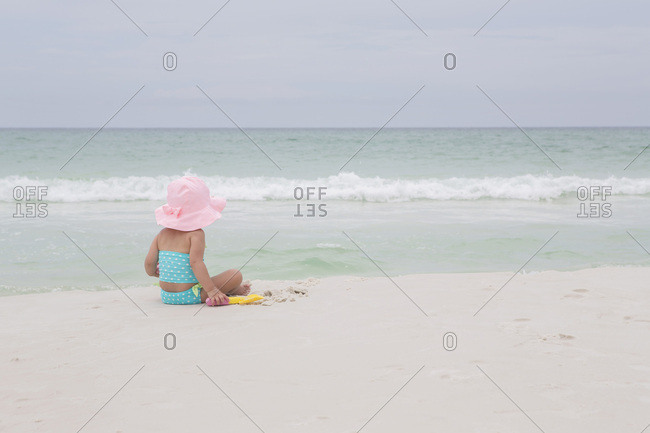 Back View of Toddler Girl wearing Sunhat on Beach looking out at Ocean, Destin, Florida, USA