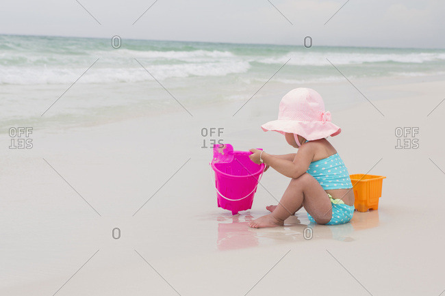 Toddler Girl Playing with Shovel and Bucket in Sand on Beach, Destin, Florida, USA