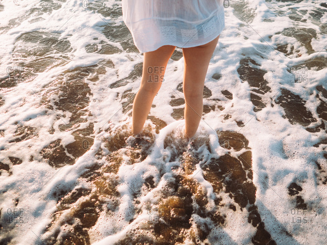 Female legs in sea foam.