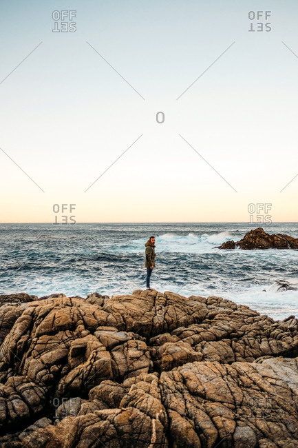 Amazing seascape with man standing on rocky coast