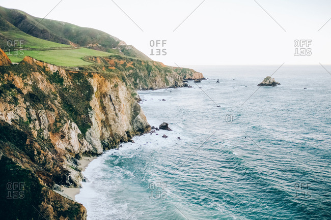 The cliff with the green meadow and the ocean.