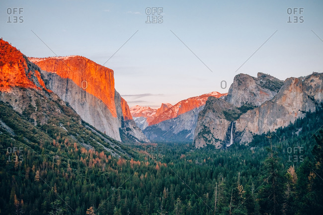 Famous Yosemite national park with rocky mountains on blue sky at sunrise.