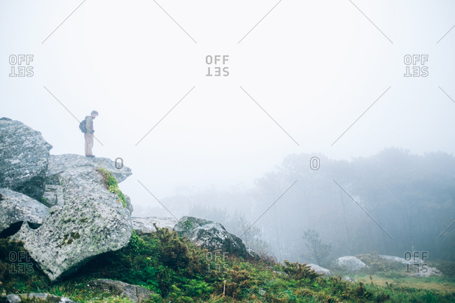 Lonely man standing on rock formation. Great landscape with fog in the air. Epic view.