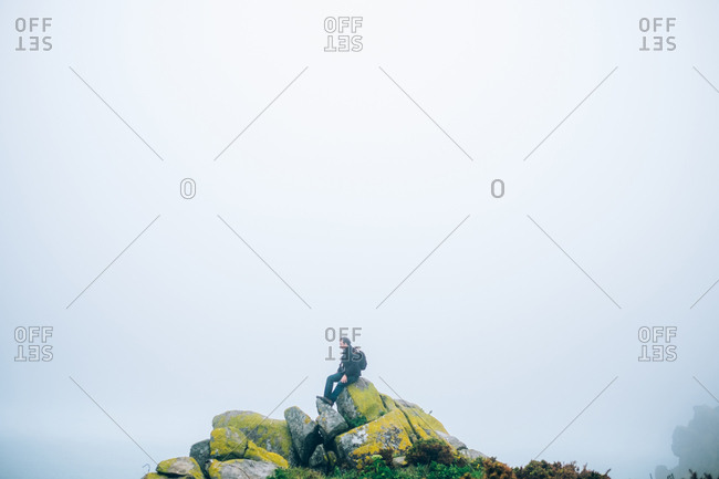 Lonely man sitting on rock formation. Great landscape with fog in the air. Epic view.