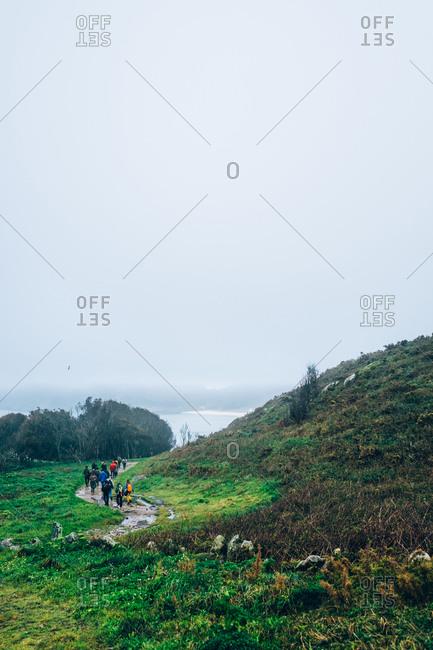 People trekking in mountain landscape in Cies Islands