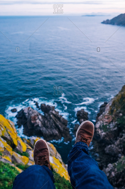 Legs of a person sitting at the edge of a cliff over the sea.