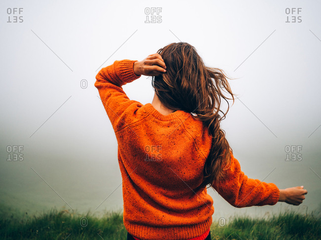 Brunette traveler with windy hair on green foggy field