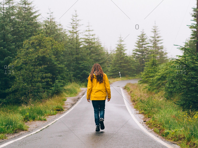 Woman in yellow raincoat walking on road in foggy morning