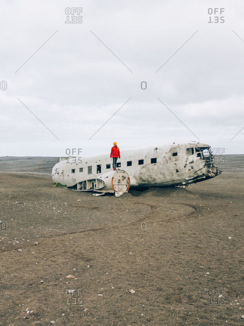 Woman in red jacket stands on old wreckage of DC plane in desert of Iceland